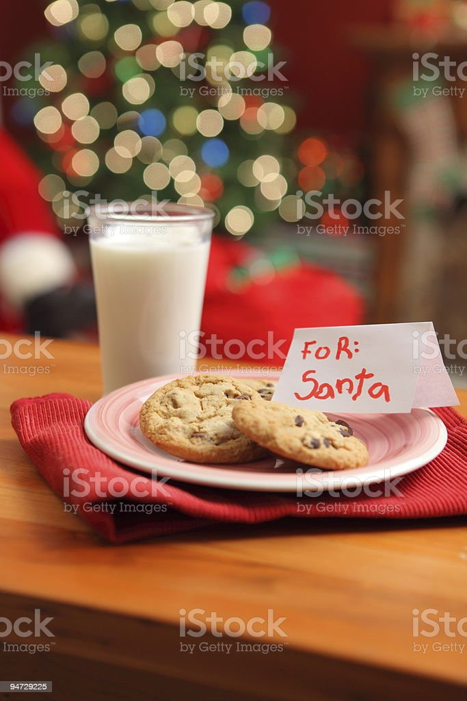 A glass of milk next to a plate of cookies left for Santa stock photo