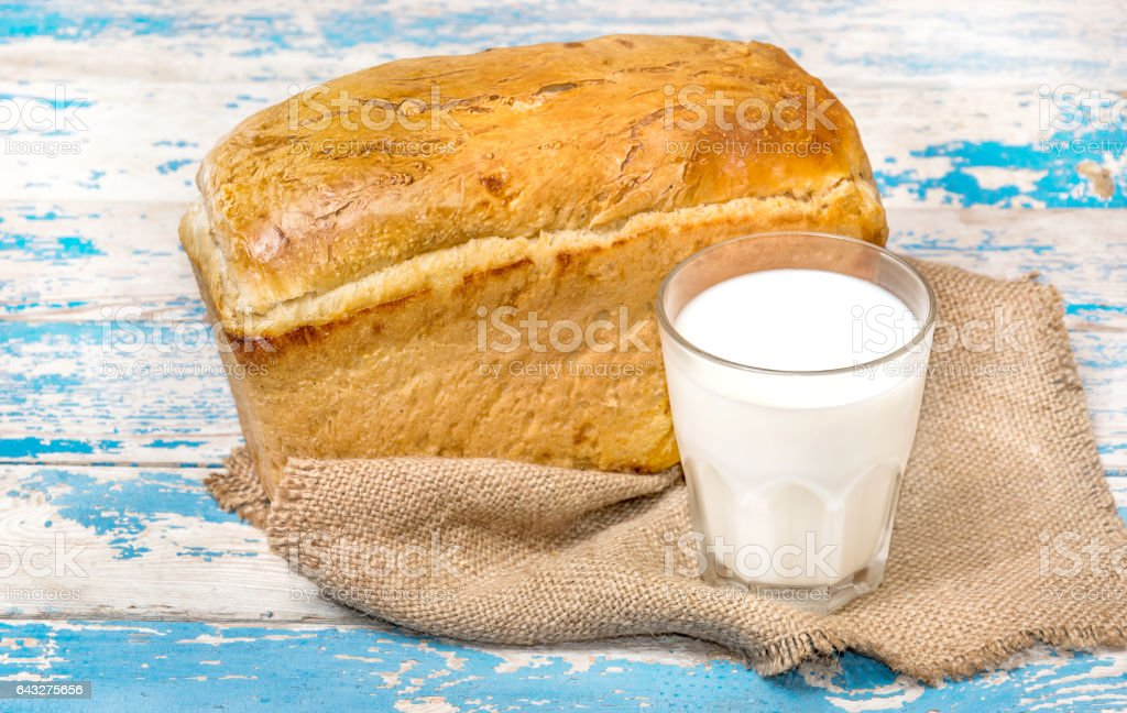 Glass of milk with bread on old wooden table. stock photo