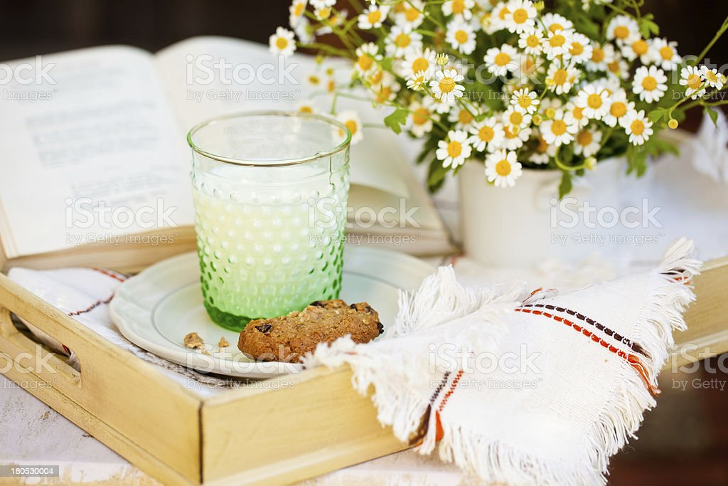 Glass of milk with cookie and flowers. royalty-free stock photo