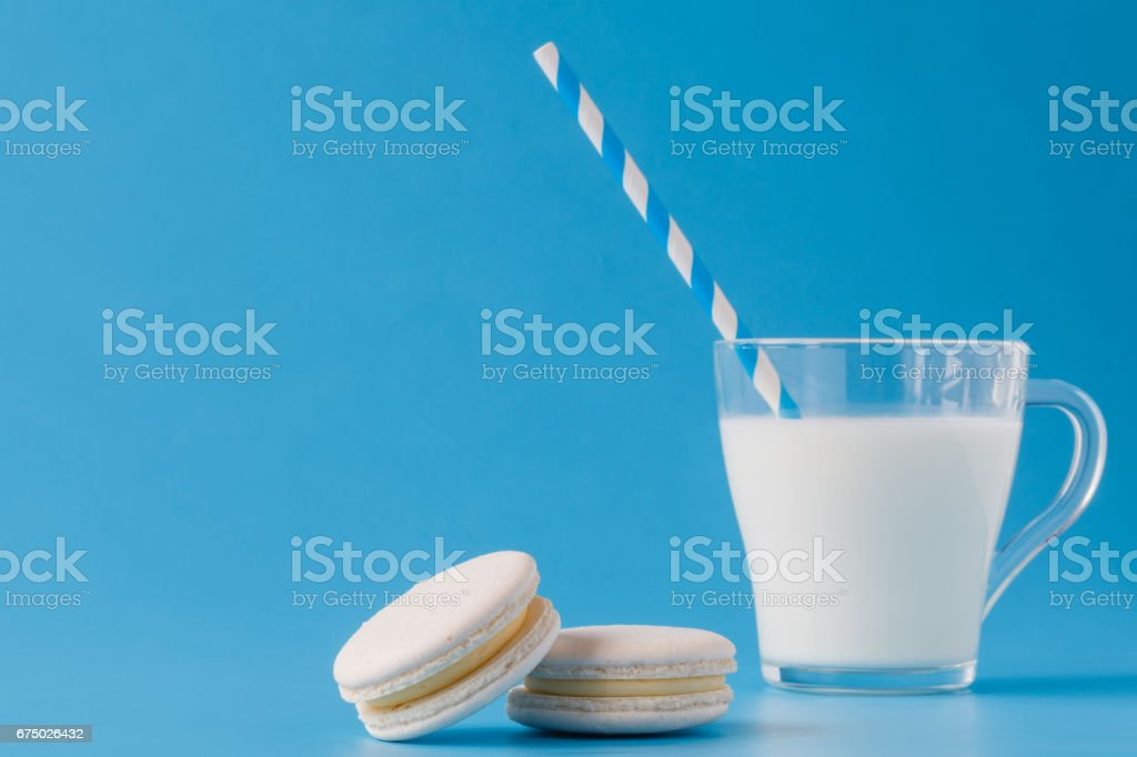 Glass of milk with french macaroon on blue background with copy space stock photo