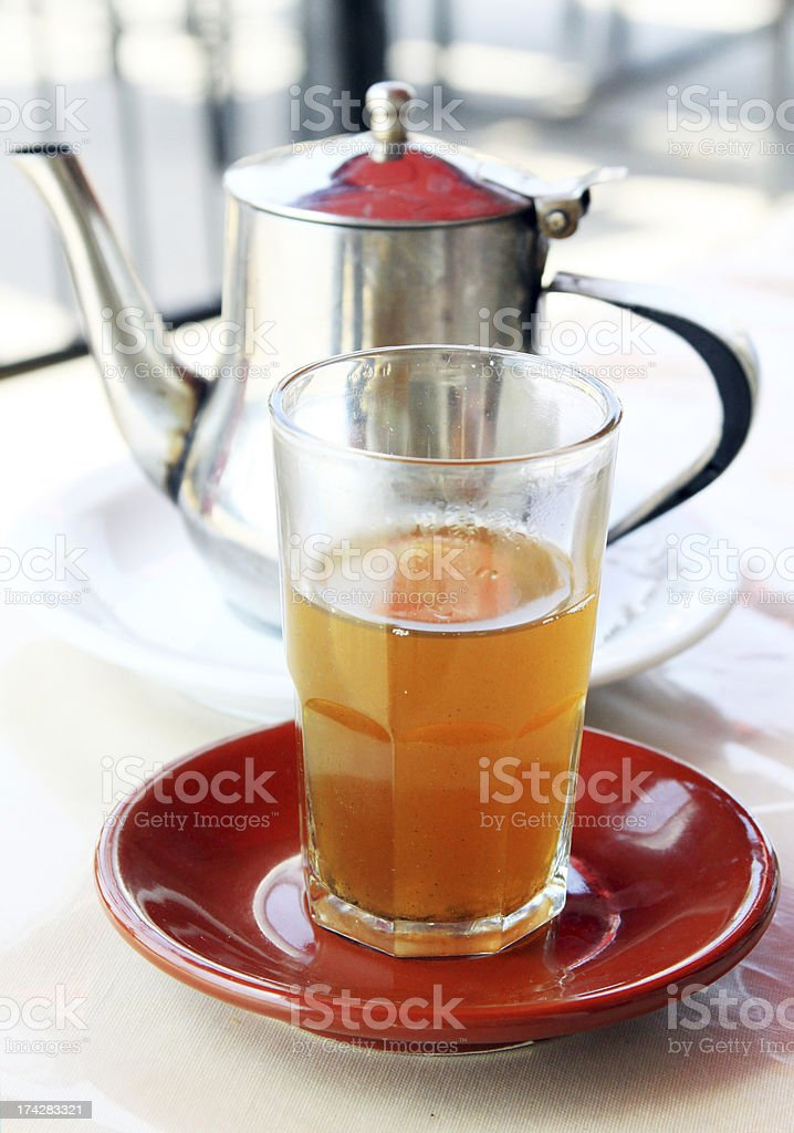 Glass of mint tea and kettle behind royalty-free stock photo