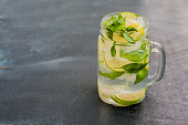 glass of mojito with lime and mint ice cube close-up