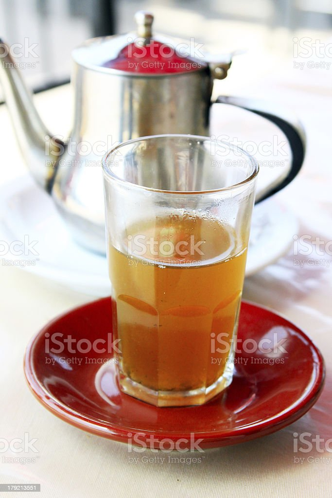 Glass of moroccan mint tea and kettle behind royalty-free stock photo