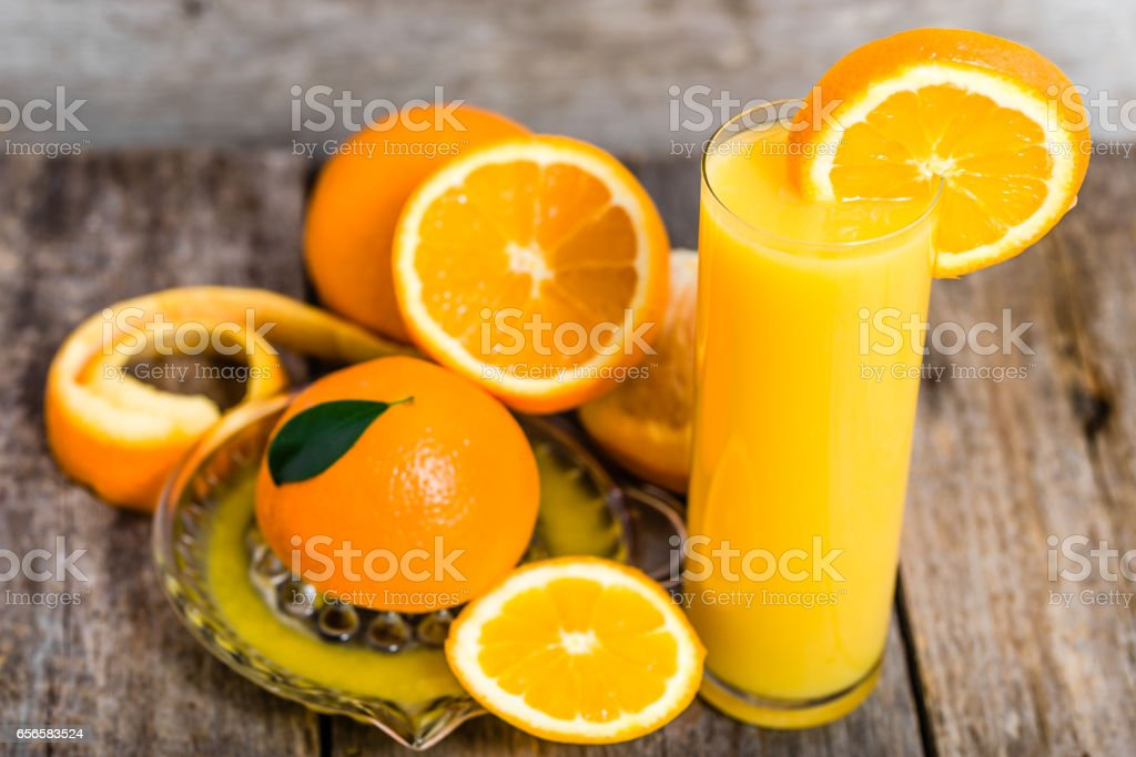 Glass of orange juice and fresh orange fruits on rustic wooden table stock photo