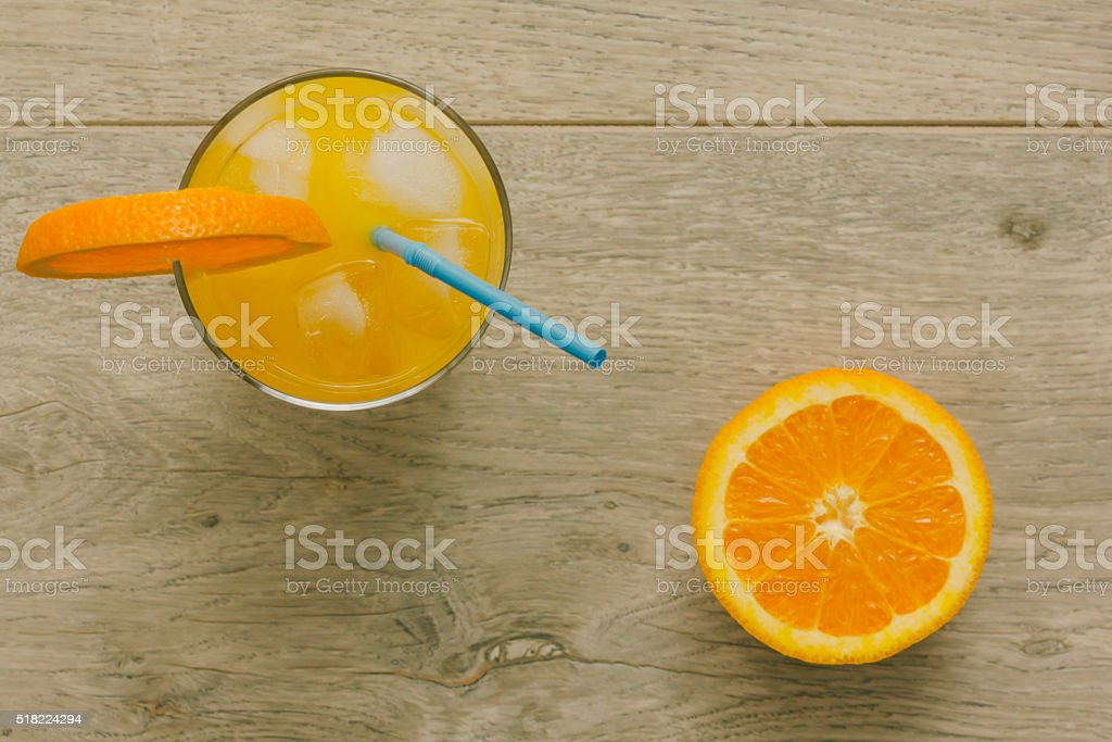 Glass of orange juice and sliced orange. Directly above view. stock photo