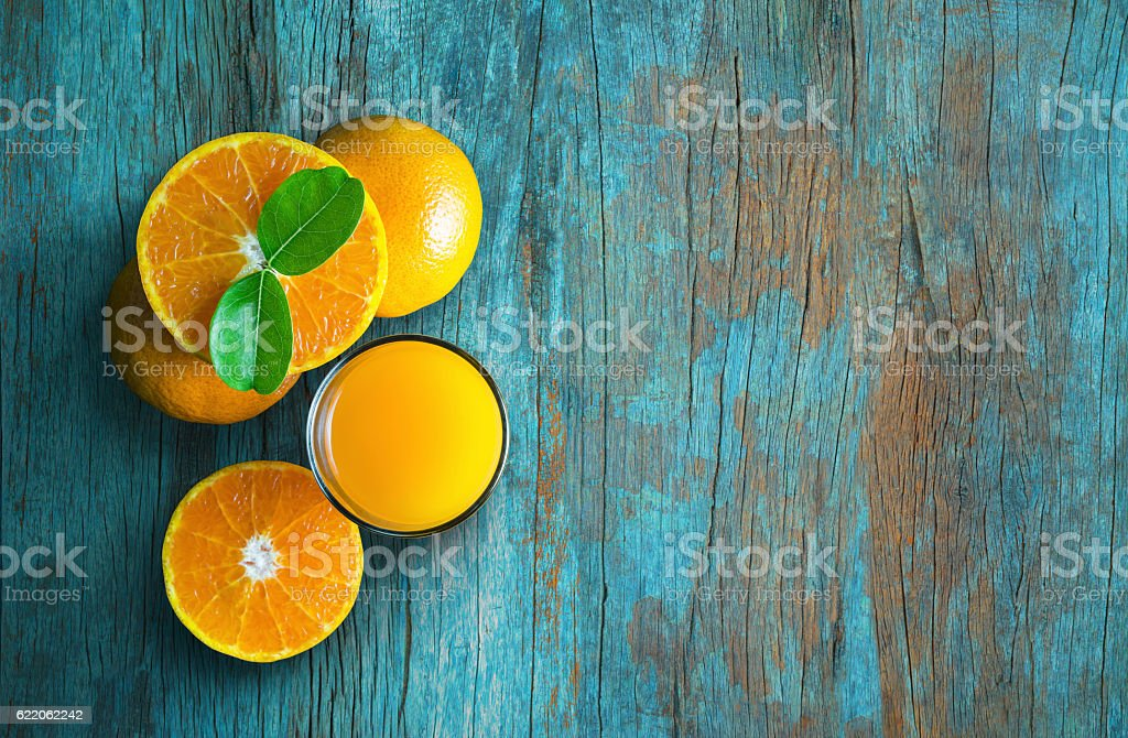 Glass of orange juice from above on blue grunge. stock photo