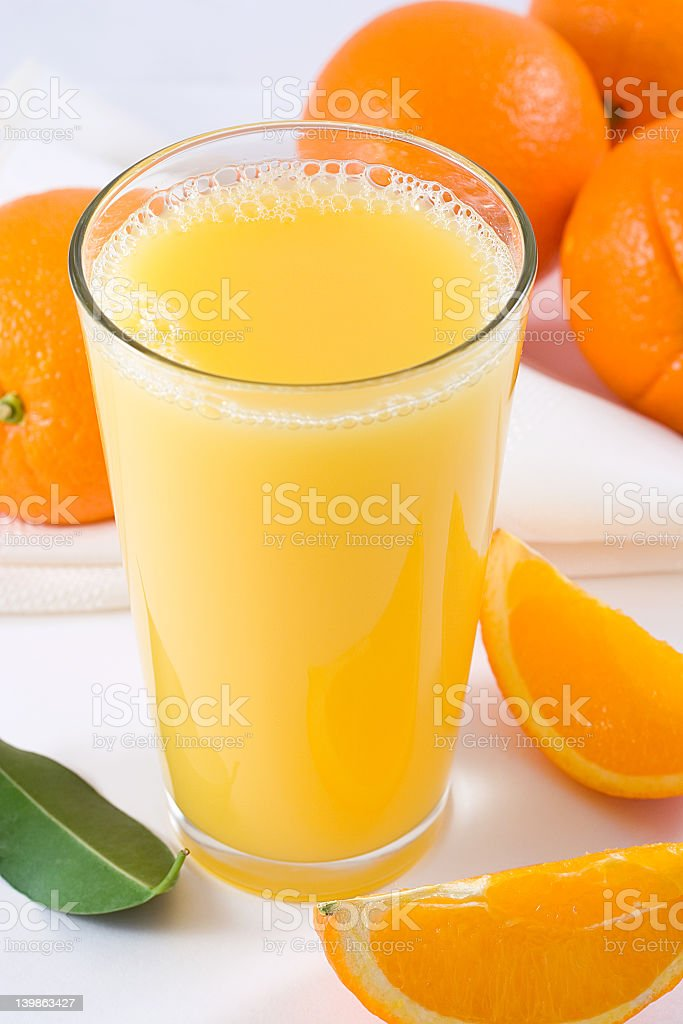 A glass of orange juice next to oranges and orange slices stock photo