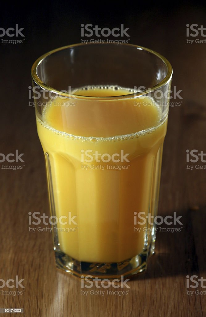 Glass of orange juice on a wooden table royalty-free stock photo