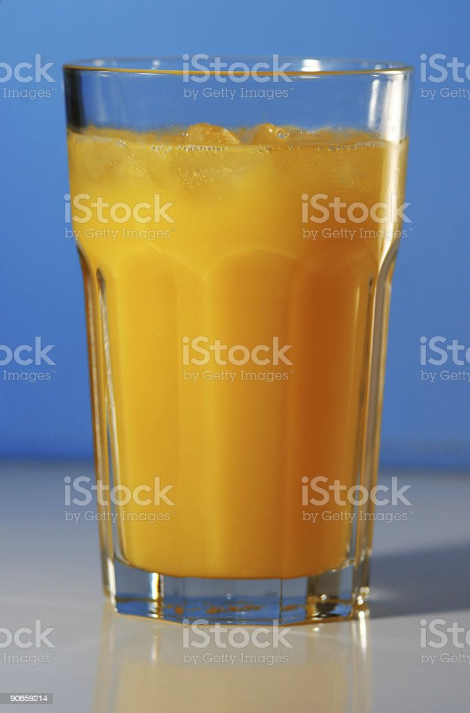 Glass of orange juice with a blue background stock photo