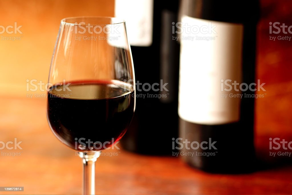 Glass of red wine and bottles with white blank label stock photo