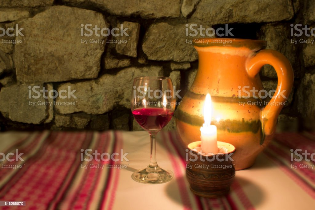 Glass of red wine and candle, dark wine-cellar with candle light stock photo
