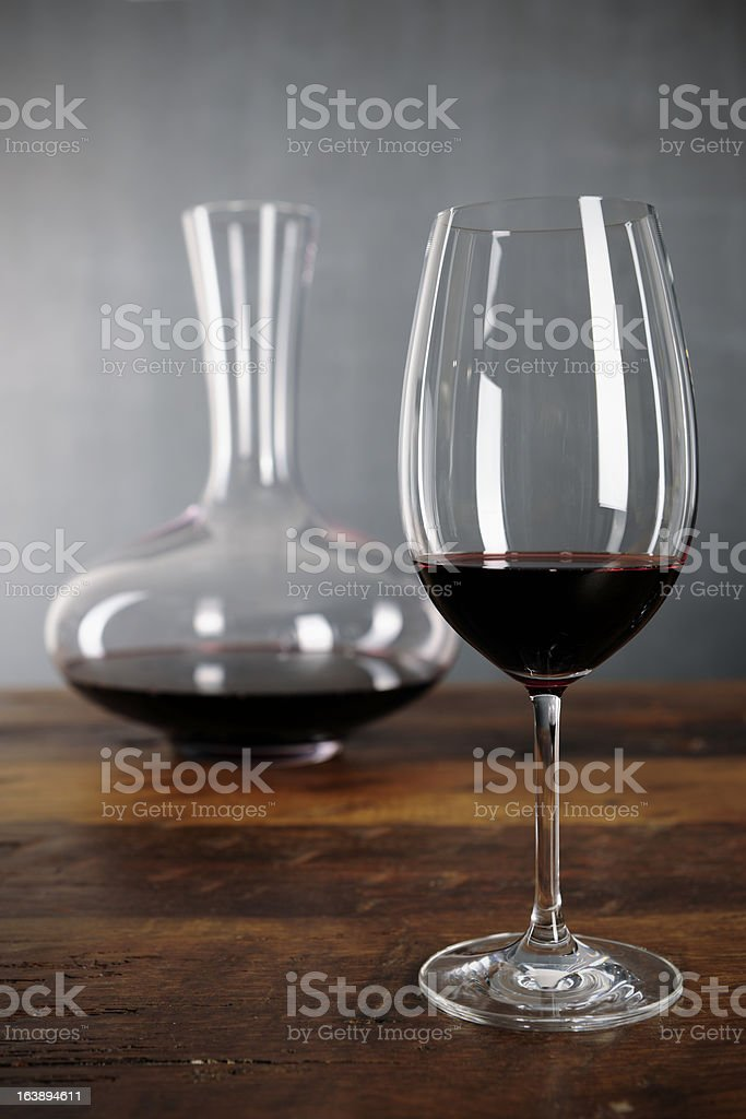 Glass of red wine and decanter on a table stock photo