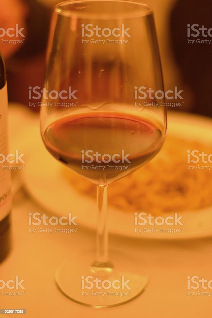 Glass of red wine and pepper and olive oil pasta stock photo