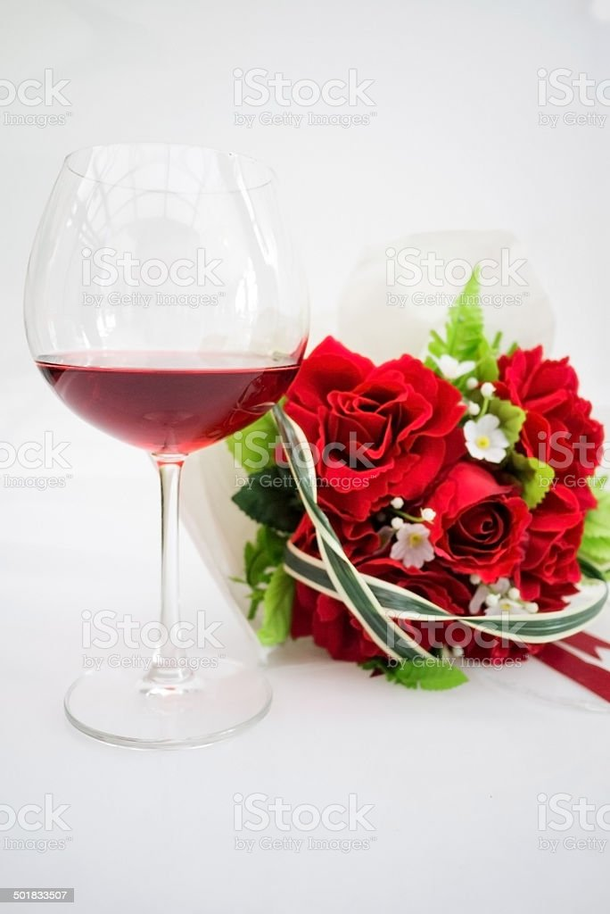 Glass of red wine and red rose bouquet stock photo