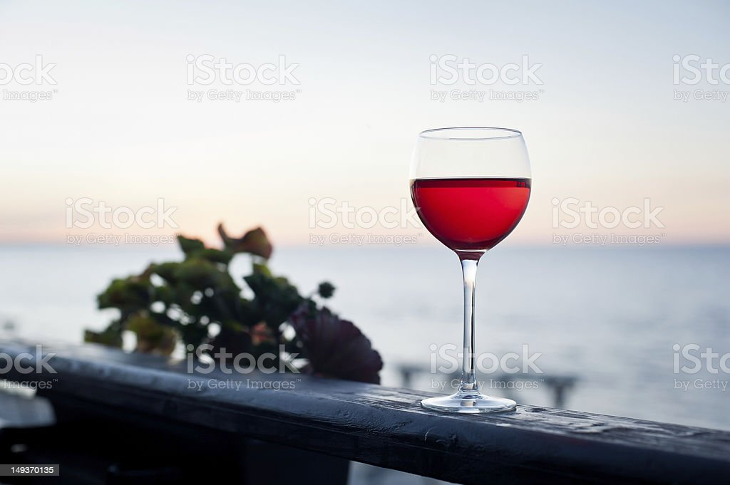 Glass of red wine at sunset on terrace stock photo