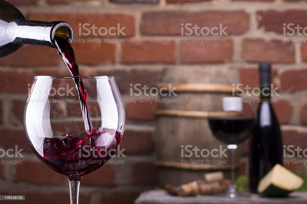 Glass of red wine being poured against a brick wall royalty-free stock photo