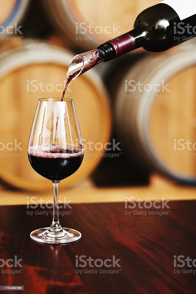 Glass of red wine being poured at winery tasting center stock photo