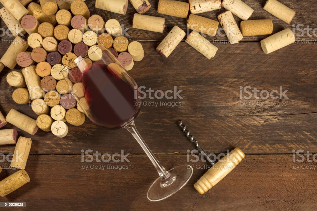 Glass of red wine, corkscrew and corks with copyspace stock photo