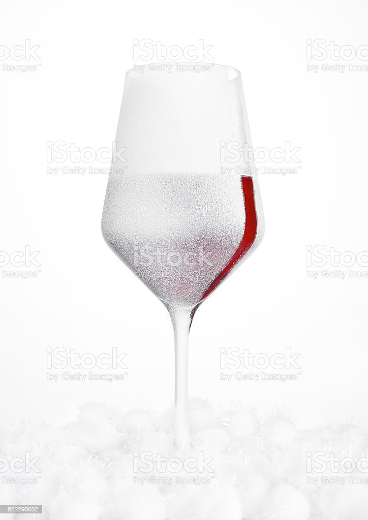 Glass of red wine covered with snow and frost stock photo