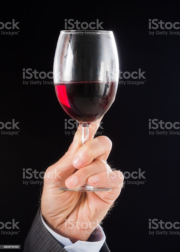 Glass of red wine held against light by man's hand stock photo