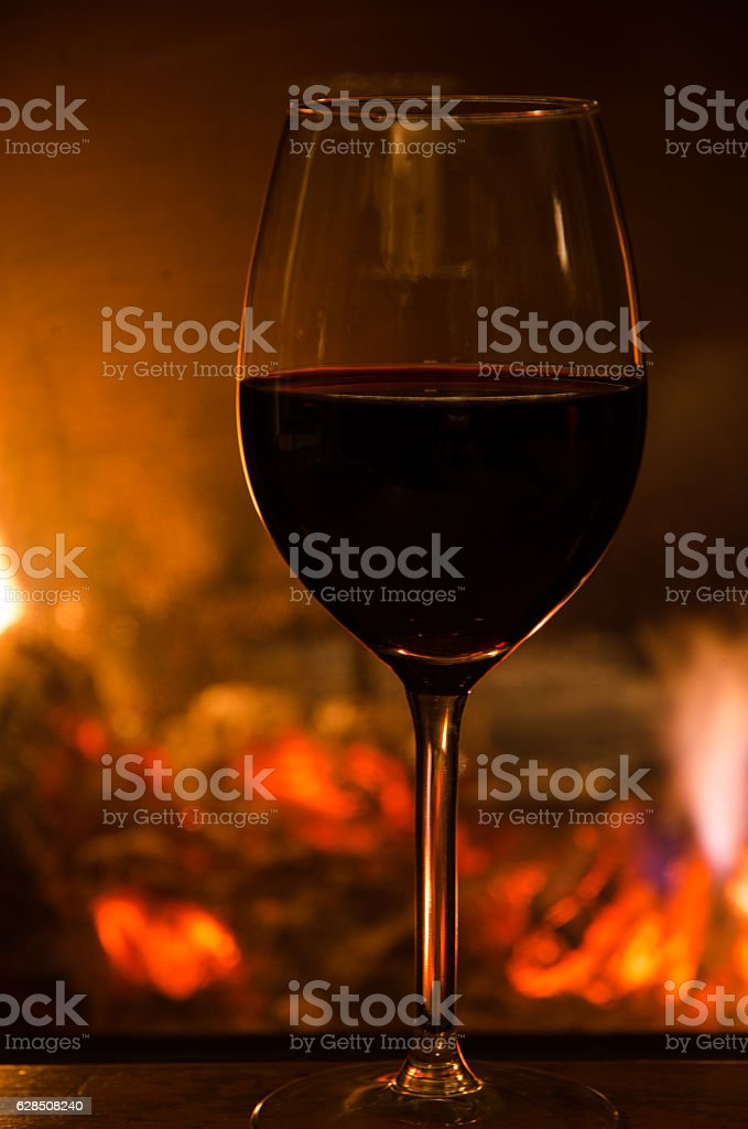 Glass of red wine in front of a fireplace stock photo