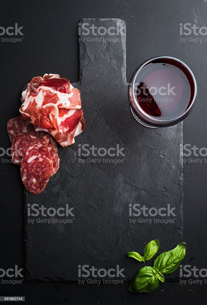 Glass of red wine, meat appetizer and basil on black stock photo