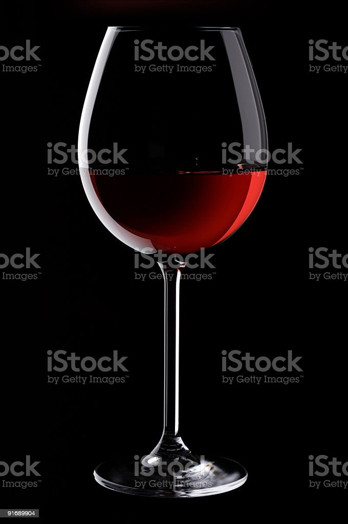 A glass of red wine on a black background royalty-free stock photo