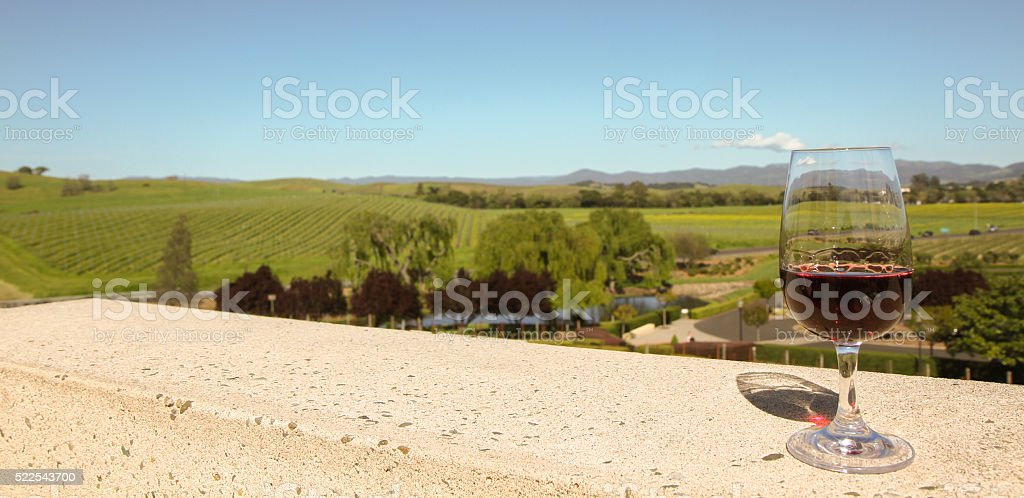 Glass of red wine on balcony overlooking Napa Valley vineyards stock photo