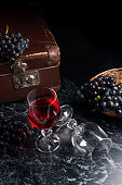 Glass of red wine on dark marble background. Blue grapes