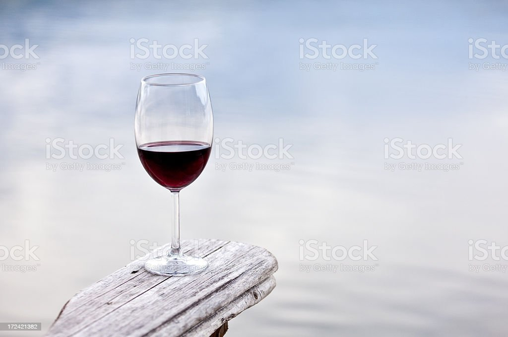 Glass of Red Wine on Rustic Adirondack Chair royalty-free stock photo