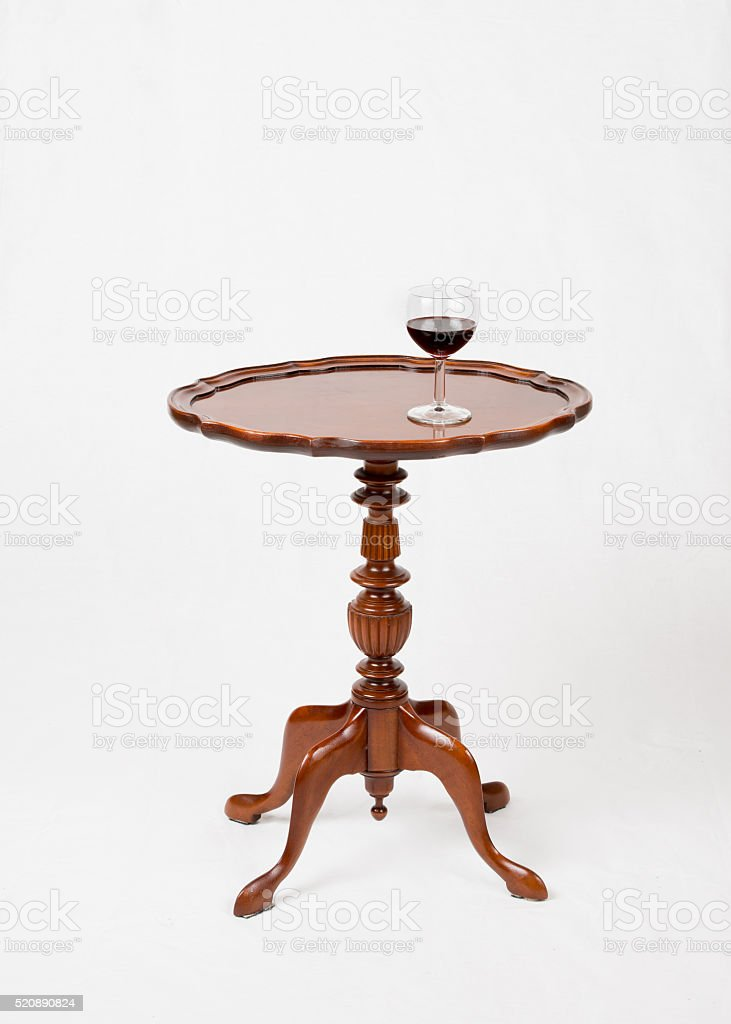 Glass of red wine on small vintage wine table stock photo