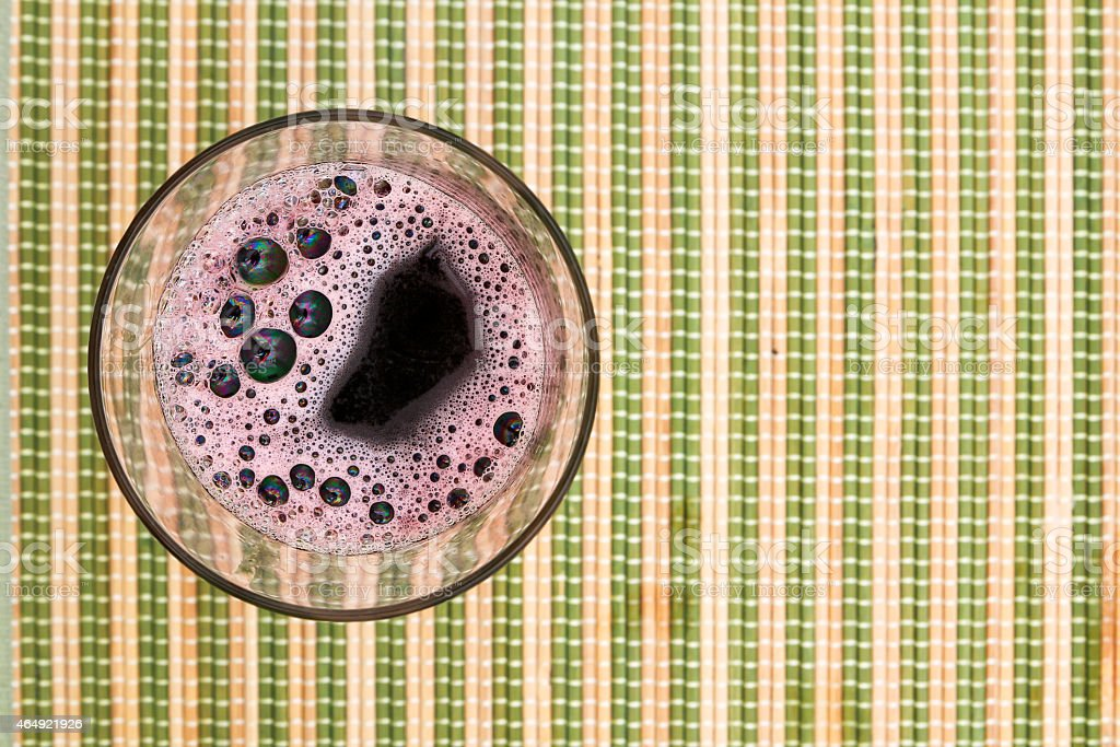 Glass of red wine on the mat stock photo