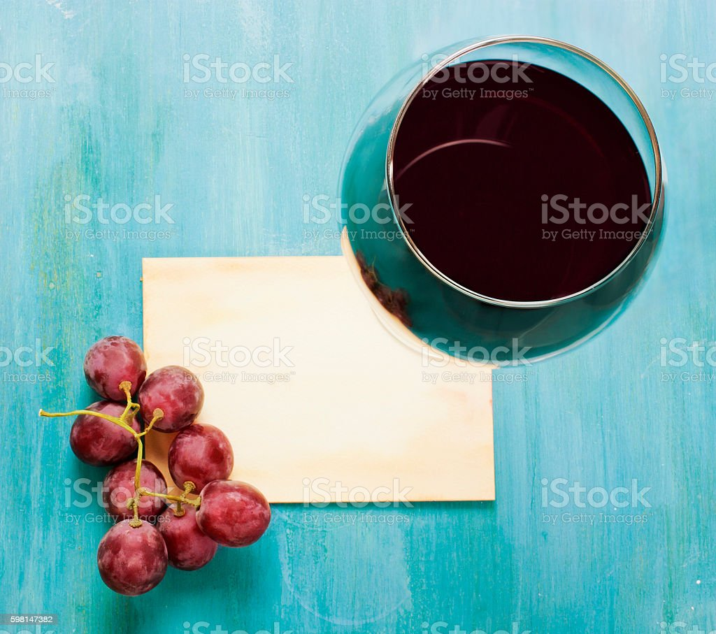 Glass of red wine with grapes and blank old paper stock photo