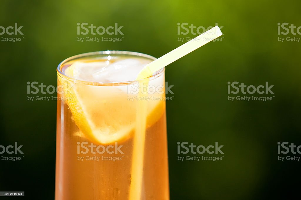Glass of Refreshing Iced Tea With Lemon Outdoors stock photo