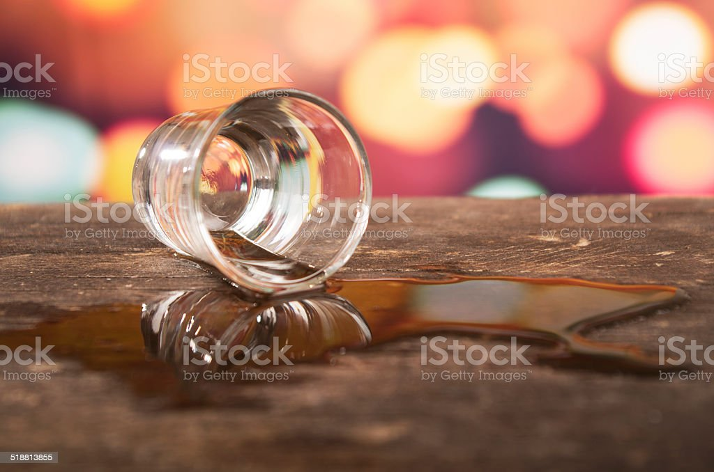 glass of rum whiskey over defocused lights background stock photo