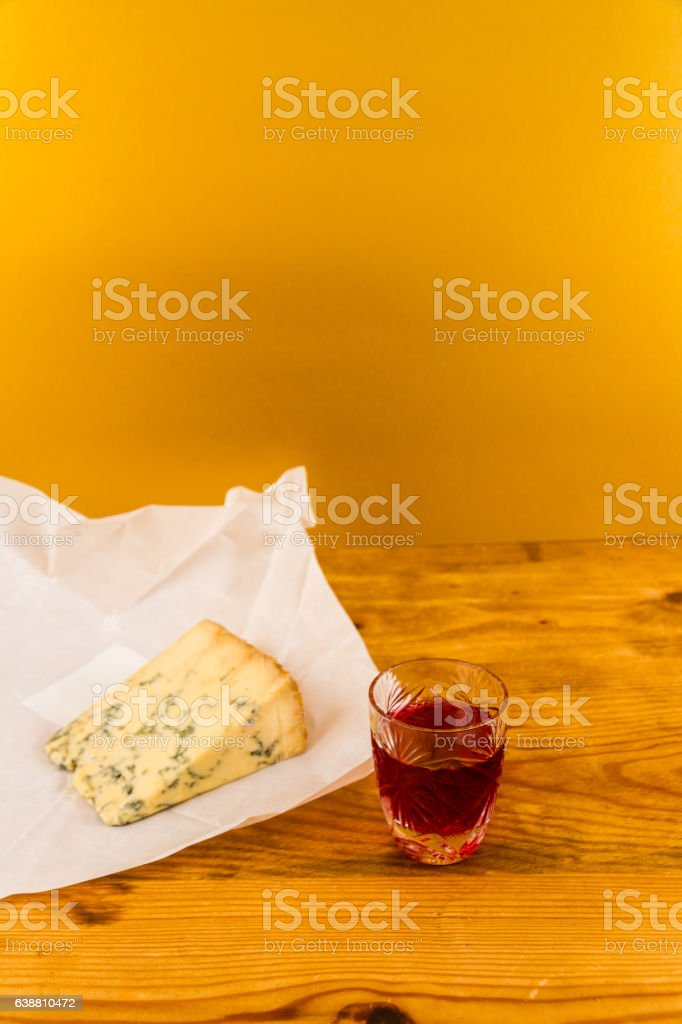 Glass of sloe gin with stilton cheese stock photo