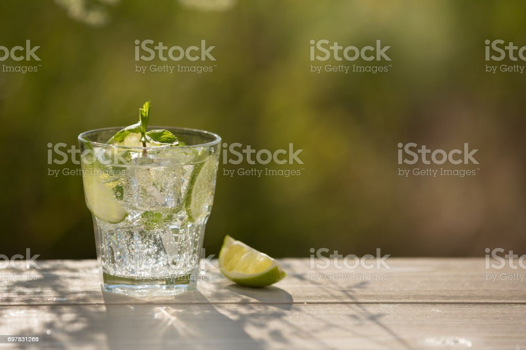 A glass of soda water on an old board, on the nature stock photo