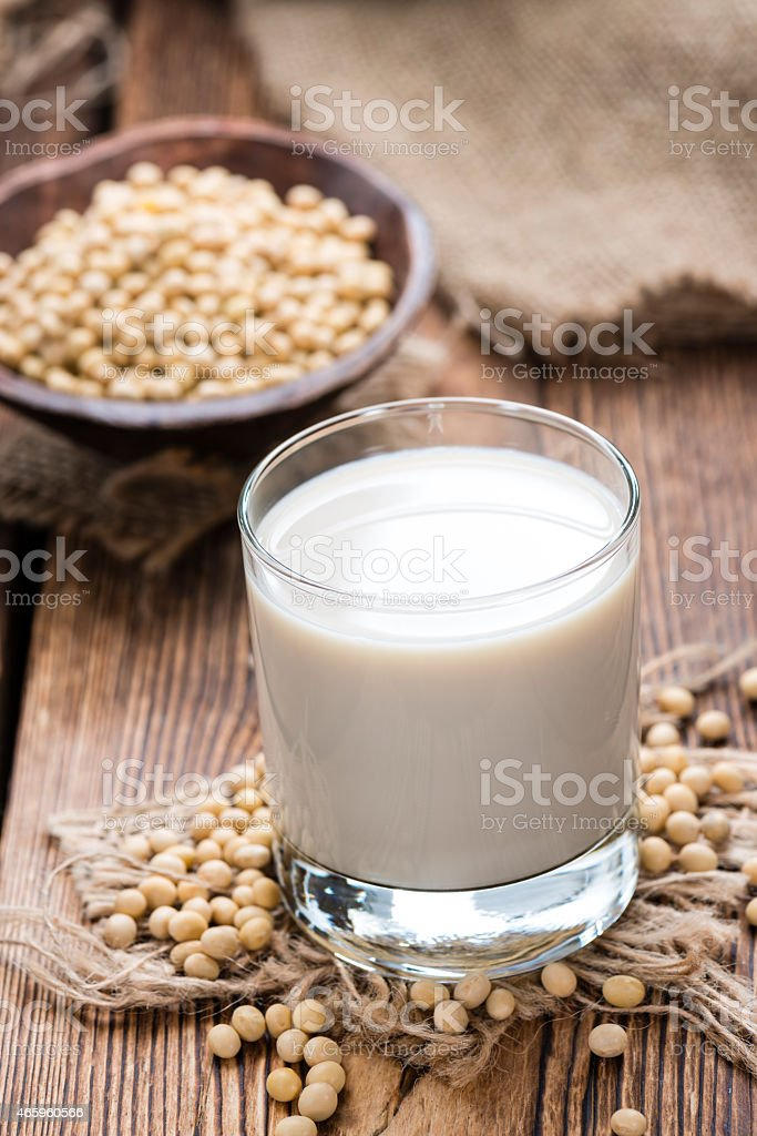 Glass of soy milk with some soy beans stock photo