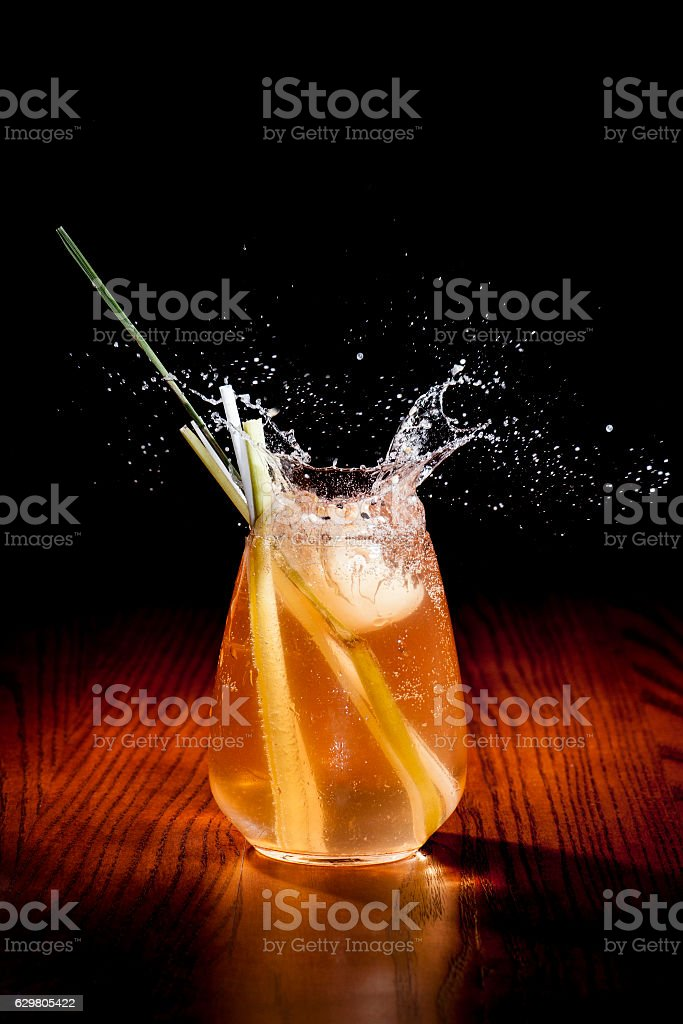 Glass of splashing cocktail with water chesnut and lemongrass stock photo