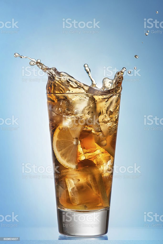 Glass of splashing iced tea with lemon stock photo