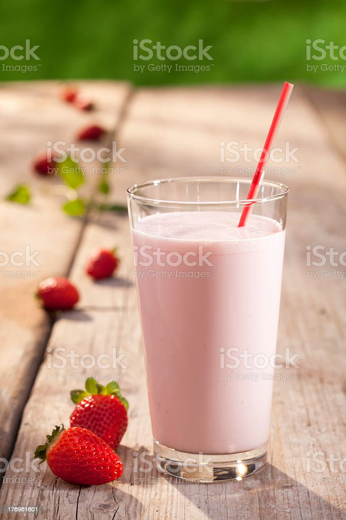 A glass of strawberry milk on a wooden table outside stock photo
