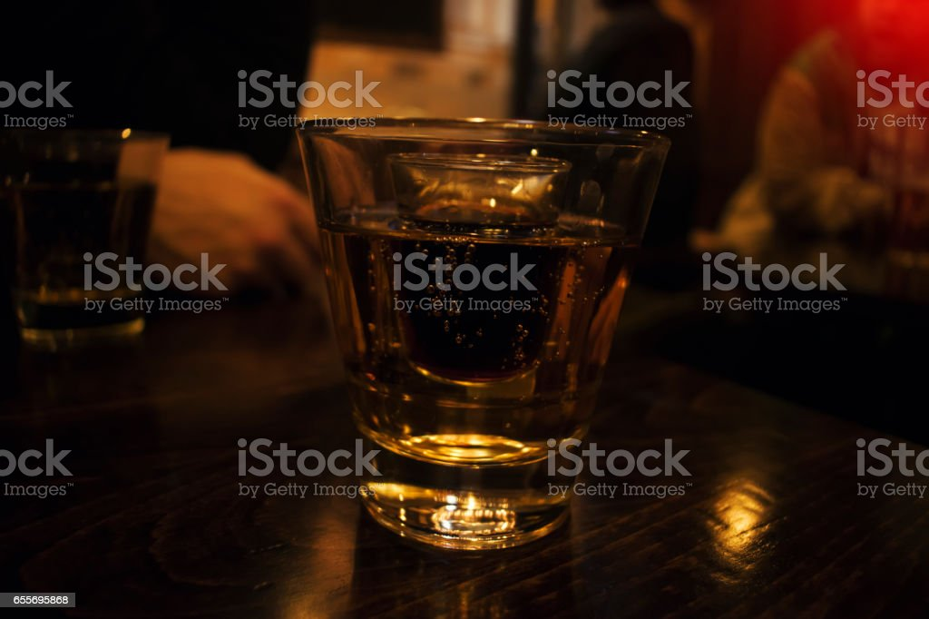 A glass of Strong alcohol inside a glass of energizer stock photo