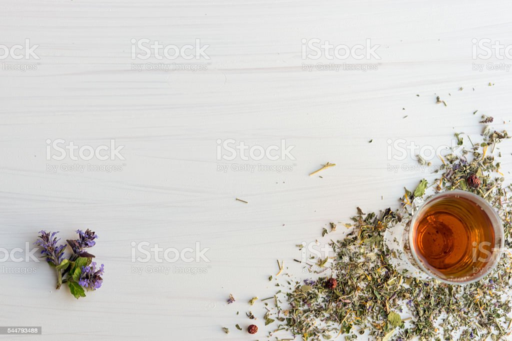Glass of tea on table with herbs stock photo