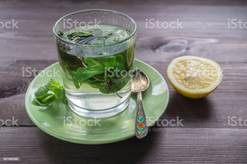 glass of tea with mint and a lemon on a dark table stock photo