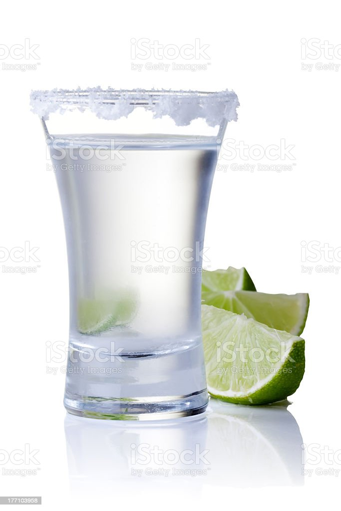 Glass of tequila with lemon on white background stock photo