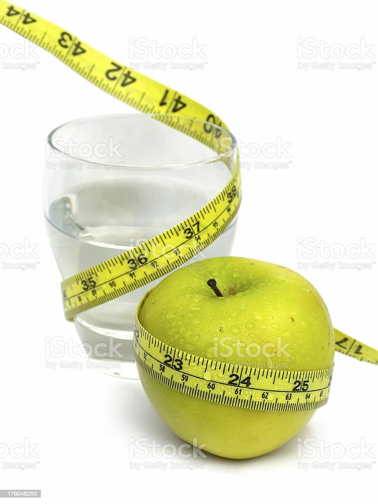 Glass of Water and Green Apple with measuring tape royalty-free stock photo