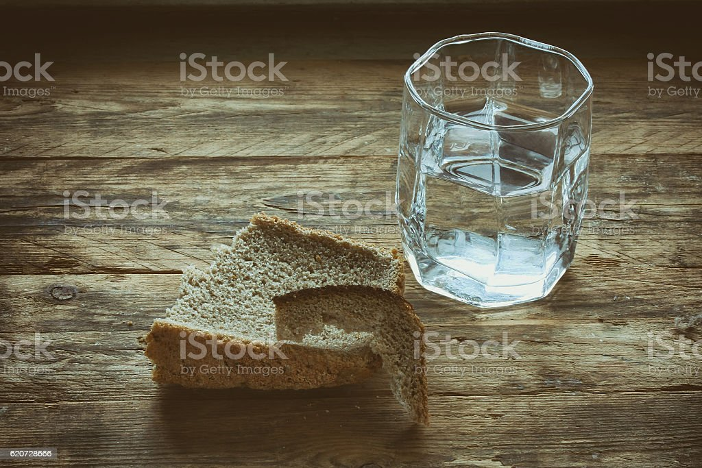 glass of water and hunk black bread stock photo