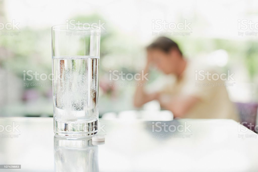 Glass of water and pill with unhappy man in background royalty-free stock photo