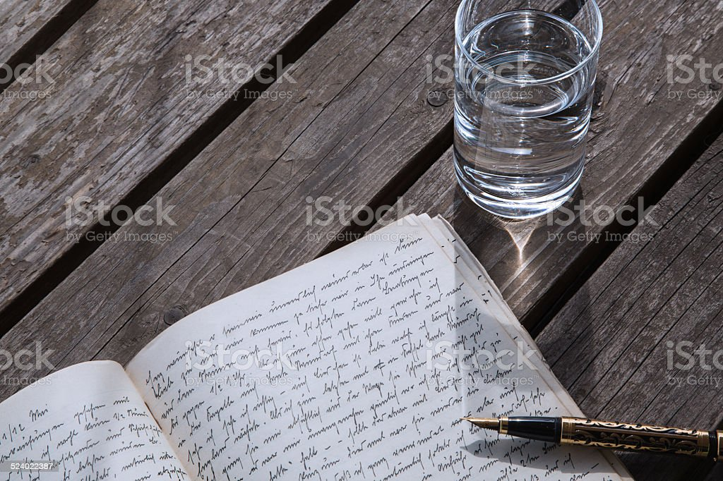 glass of water and writing in a book stock photo
