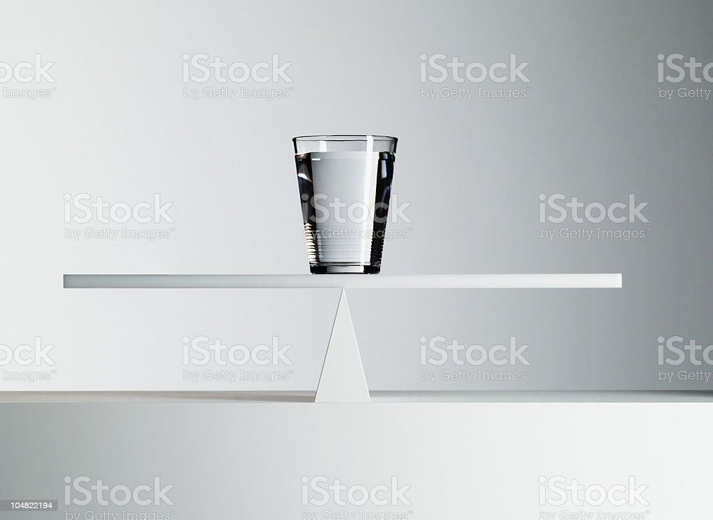 Glass of water balancing on middle of seesaw stock photo